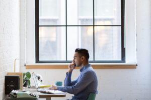 man at desk near window